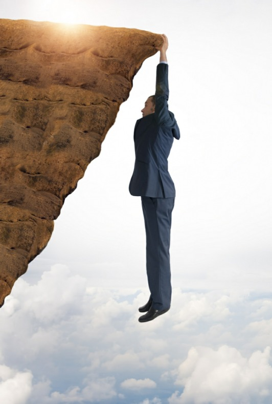 man hanging from cliff by fingers metaphor